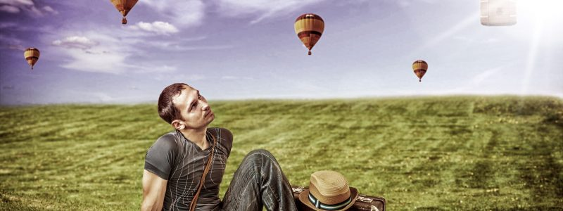 Young man traveler sitting on a fresh green grass and lookig to a flying balloons  in blue sky